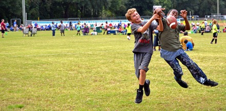 SIDELINE SUPPORT - Miller Dahl, 12, and Troy Aadams, 11, pass the time on the sidelines by playing in a football scrimmage. The boys have older and younger relatives particpating in the Alachua Rec Center's Championship soccer tournament. (photo by Harley O'Neill)